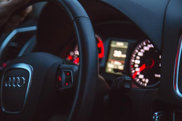 black lit up dashboard of audi with steering wheel